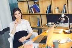 Schwangere Geschäftsfrau, die an der Büromutterschaft sitzt arbeitet, Snack essend stockbild
