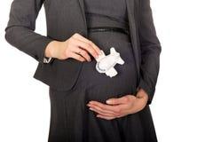 Schwangere Geschäftsfrau, die flaches Modell hält Stockfotos