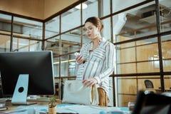 Schwangere Geschäftsfrau, die nach der Arbeit ihre Vitamine nimmt lizenzfreies stockbild