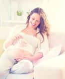 Schwangere glückliche Frau, die Babyschuhe hält Stockbild