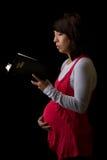 Schwangere hispanische Frau, welche die Bibel liest Lizenzfreies Stockbild