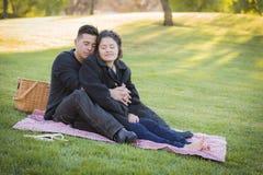 Schwangere hispanische Paare im Park draußen Stockfoto