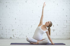 Schwangere junge Frau, die pränatales Yoga tut Seitenausdehnen Lizenzfreie Stockfotos