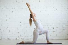 Schwangere junge Frau, die Yoga Virabhadrasana 1 Haltung tut Stockfotografie