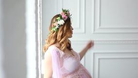 Schwangere junge Frau in einem ankleidenden peignoir steht am Fenster stock video footage