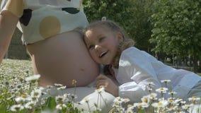 Schwangere junge Frau mit einem Kind im Park unter Blumen stock video footage
