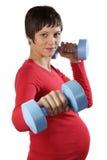 Schwangere junge Frau mit Gewichten Stockfotografie