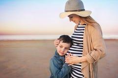 Schwangere junge Frau mit seinem kleinen Sohn steht auf einem Strand und setzt Hände auf einen Bauch stockfotos