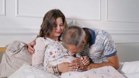 Schwangere küssender Frau und Mann beim Sitzen im Bett stock footage