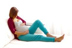 Schwangere kaukasische Frau, die sich zu Hause auf der Couch entspannt stockfoto
