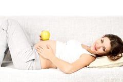 Schwangere Lügen mit Apfel lizenzfreie stockfotografie