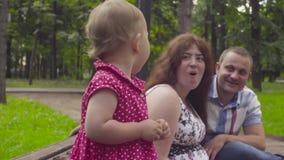 Schwangere Mutter, Baby und Vati, die auf einer Bank sitzt stock footage