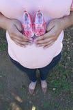 Schwangere Mutter, die Babyschuhe hält Stockbild