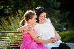 Schwangere Mutter, die ihre nette Tochter umfasst Lizenzfreie Stockbilder