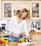 Schwangere Mutter, die Lebensmittel in der Küche zubereitet Lizenzfreie Stockfotos