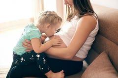 Schwangere Mutter, die mit nettes daugher küssendem dickem Bauch sitzt stockfotografie