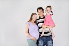 Schwangere Mutter, glücklicher Vater und Tochter Lizenzfreie Stockfotos
