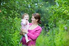 Schwangere Mutter mit ihrer ein jährigen Babytochter Lizenzfreie Stockfotos