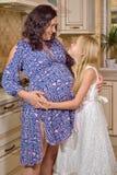 Schwangere Mutter mit ihrer Tochter Stockfotos