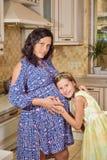 Schwangere Mutter mit ihrer Tochter Lizenzfreie Stockfotos