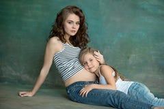 Schwangere Mutter mit jugendlich Tochter Familienstudioporträt über blauem Hintergrund stockfotografie