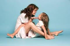 Schwangere Mutter mit jugendlich Tochter Familienstudioporträt über blauem Hintergrund lizenzfreies stockbild