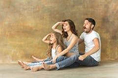 Schwangere Mutter mit jugendlich Tochter und Ehemann Familienstudioporträt über braunem Hintergrund stockfoto
