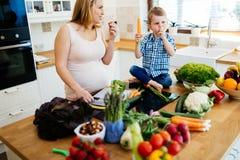 Schwangere Mutter und Kind, die Mahlzeit vorbereitet lizenzfreies stockbild