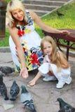 Schwangere Mutter und kleine Tochter ziehen Tauben im Sommer ein Stockfotos