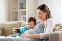 Schwangere Mutter und Sohn mit Smartphone zu Hause stockbilder