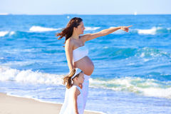 Schwangere Mutter und Tochter auf dem Strand Stockbilder