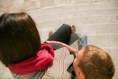 Schwangere Paare, die auf Treppe sitzen Stockbild