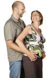 Schwangere Paare, die einander lächelnd betrachten Stockfotografie