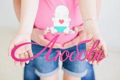 Schwangere Paare, die hölzerne dekorative Buchstaben halten stockbilder