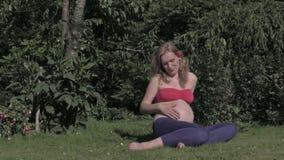 Schwangere Palme der jungen Frau ihr Bauch, genießen Sonne im Park stock footage