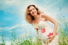 Schwangere schöne Frau mit überreicht Bauch Lizenzfreie Stockfotos