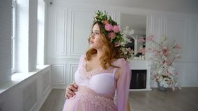 Schwangere schöne junge Frau im lila peignoir und im Blumenhauptkranz geht auf Luxusraum stock video