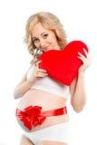 Schwangere Schönheit, die rotes Herzkissen in ihren Händen lokalisiert auf weißem Hintergrund hält Stockfotografie