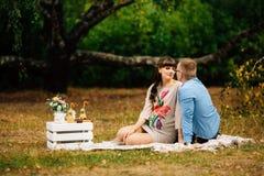 Schwangere Schönheit mit ihrem hübschen Ehemann, der süß draußen im Herbst auf Picknick stillsteht Lizenzfreie Stockfotos