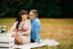 Schwangere Schönheit mit ihrem hübschen Ehemann, der süß draußen im Herbst auf Picknick stillsteht Lizenzfreies Stockfoto