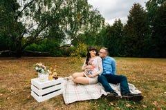 Schwangere Schönheit mit ihrem hübschen Ehemann, der süß draußen im Herbst auf Picknick stillsteht Stockfotos