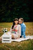 Schwangere Schönheit mit ihrem hübschen Ehemann, der süß draußen im Herbst auf Picknick stillsteht Stockbilder