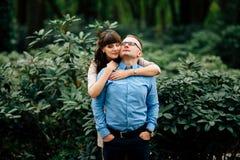 Schwangere Schönheit und ihr reizendes Umarmen des hübschen Ehemanns im Park Lizenzfreie Stockfotografie