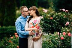Schwangere Schönheit und ihr reizendes Umarmen des hübschen Ehemanns im Park Stockfotografie