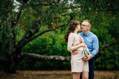Schwangere Schönheit und ihre reizende Entspannung des hübschen Ehemanns auf Natur, haben Picknick im Herbstpark Lizenzfreie Stockbilder