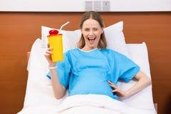 Schwangere Schale mit Getränk haltene und beim Lügen blinkende Frau des Kaukasiers im Krankenhausbett Lizenzfreie Stockfotos
