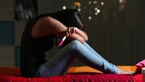 Schwangere traurige jugendlich Beschwerde, einen Schwangerschaftstest halten