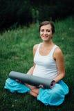 Schwangere Yogafrau im Lotussitz mit Mattenporträt im Park auf dem Gras, Atmung, dehnend, Statik aus Lizenzfreies Stockbild