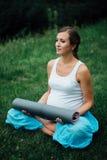 Schwangere Yogafrau im Lotussitz mit Mattenporträt im Park auf dem Gras, Atmung, dehnend, Statik aus Lizenzfreie Stockbilder