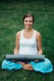 Schwangere Yogafrau im Lotussitz mit Mattenporträt im Park auf dem Gras, Atmung, dehnend, Statik aus Stockbild